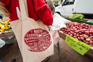 Pedestrians shop for fresh potatoes and other produce while walking around the Dane County Farmers' Market that circles the Wisconsin State Capitol in downtown Madison, Wis., during a spring morning on June 20, 2015. Attending the Farmers' Market is a favorite weekend activity for many University of Wisconsin-Madison students and members of the Madison community. (Photo by Jeff Miller/UW-Madison)