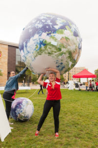 Photo of Bre Nehls with an inflatable earth