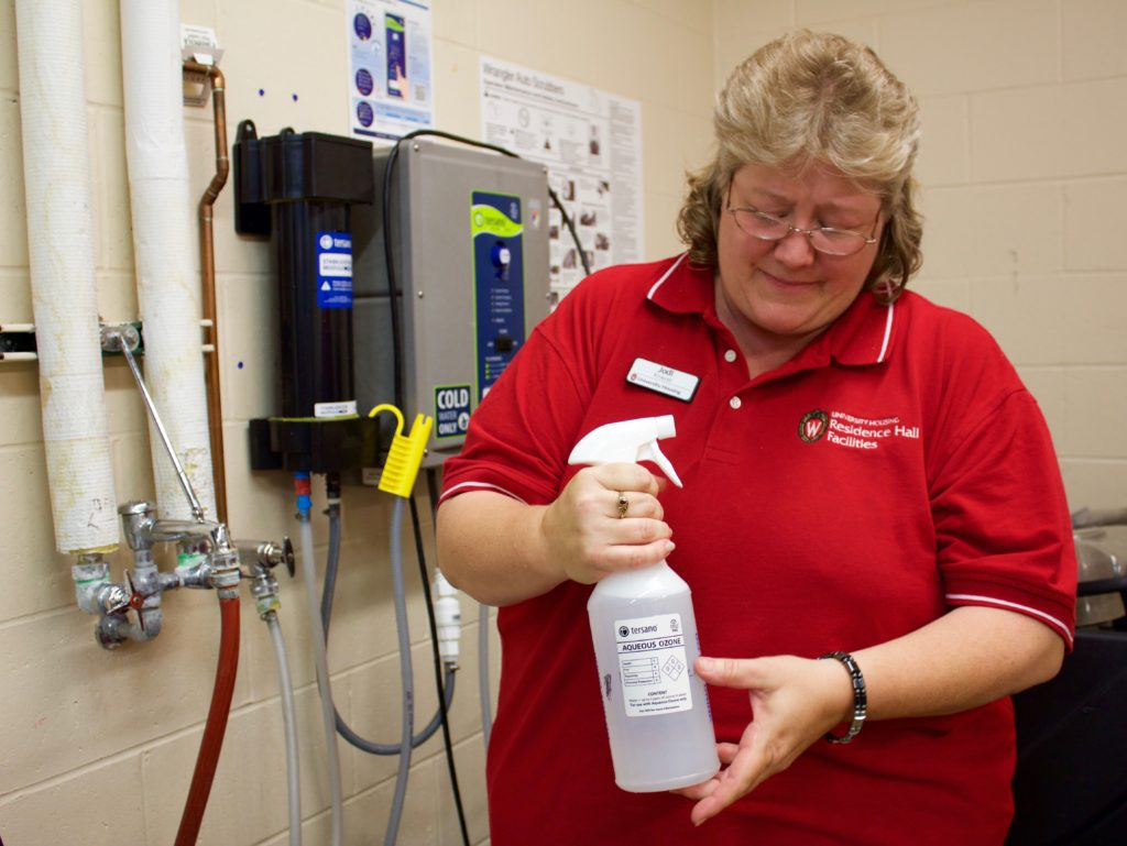 Jodi Krause shows a bottle of aqueous ozone cleaning solution