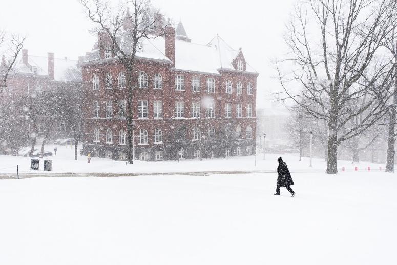 Person trudges across Bascom Hill near Science Hallin snowstorm.