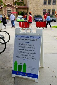 Housing students moving in stream by a hydration station sign. Photo by Trina La Susa.
