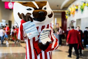 "UW-Madison mascot Bucky Badger helps volunteers distribute complimentary copies of ""The Death and Life of the Great Lakes"" following the Chancellor's Convocation for New Students at the Kohl Center at the University of Wisconsin-Madison on Sept. 4, 2018. (Photo by Jeff Miller / UW-Madison)"