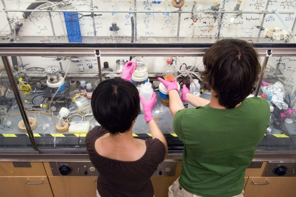 Graduate students Lingyin Li (left) and Ratmir Derda prepare materials under a fume hood in Laura L. Kiessling's research lab in the Chemistry Building at the University of Wisconsin-Madison