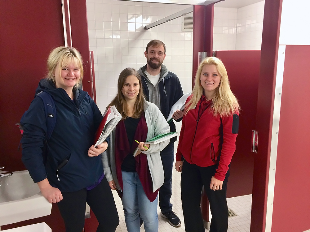 Students Emma Nelson, Gabby Campagnola, and Dan Mrotek (from left to right) and former University Housing Sustainability Coordinator Breana Nehls walk through the residence halls to inventory the toilets. Photo by Ian Aley.