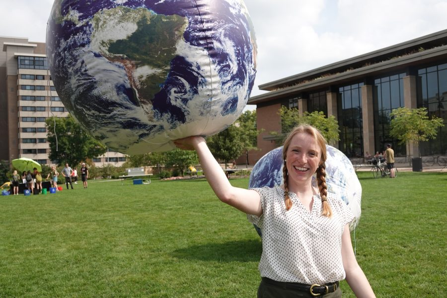 UW-Madison graduate student Audrey Stanton holds up an inflatable earth during Sustain-a-Bash 2019.