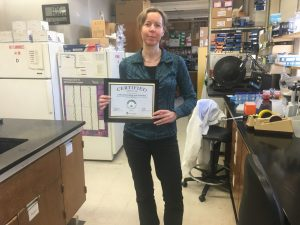 Woman holding Green Labs certificate in a lab