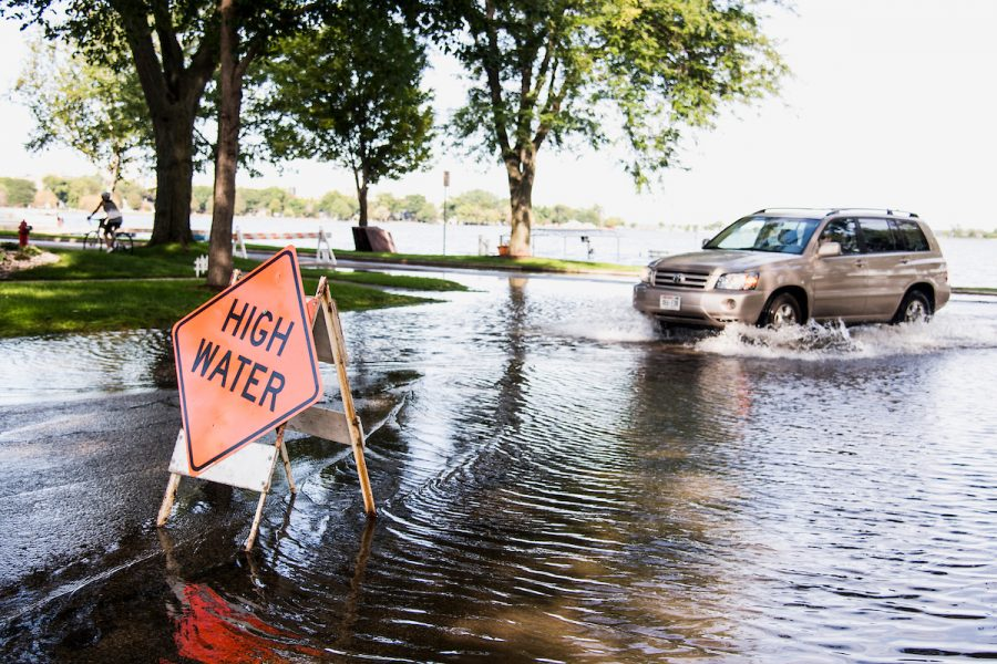 A road hazard sign warns of high-standing water flooding West Shore Drive along Monona Bay in Madison, Wis., during summer on Sept. 6, 2018.