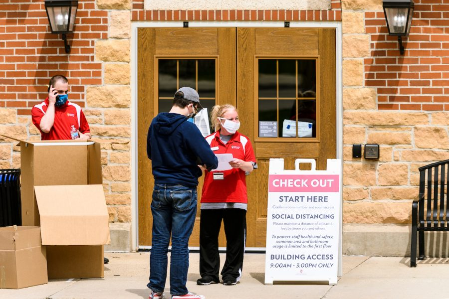 On May 2, 2020, UW Housing staff Trevor Potter, left, and Polly Bartelt check in a student at Tripp-Adams Residence Hall as some student residents return to campus to gather their belongings from UW Housing facilities at the University of Wisconsin-Madison. The staggered move-out process, occurring April 27-May 7, requires people to practice social distancing and safety protocols. Many student residents left campus for UW-Madison Spring Break in mid-March thinking the UW-Madison campus would only be temporarily closed in response to health concerns of the global coronavirus (COVID-19) pandemic. (Photo by Jeff Miller / UW-Madison)