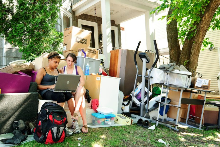 On Aug. 14, 2011, University of Wisconsin-Madison undergraduates Lisa Diaz (left) and Megan Tyson (right) are surrounded by their possessions on the lawn of their campus-area rental house during the annual Madison move-out/move-in weekend. With housing leases ending on Aug. 14 and a new leases taking effect on Aug. 15, landlords have a window of time to clean, paint and make necessary repairs. In the meantime, tenants must find temporary shelter for themselves and their belongings. (Photo by Bryce Richter / UW-Madison)