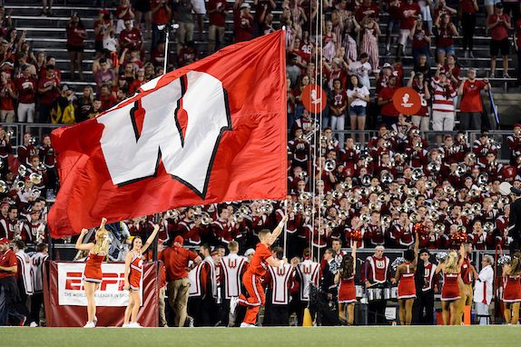 A cheerleader with the UW Spirit Squad runs a large W flag across the field during a season-opening, night football game between the Wisconsin Badgers and the Western Kentucky Hilltoppers at Camp Randall Stadium at the University of Wisconsin-Madison on Aug. 31, 2018. The Badgers won, 34-3. (Photo by Jeff Miller / UW-Madison)