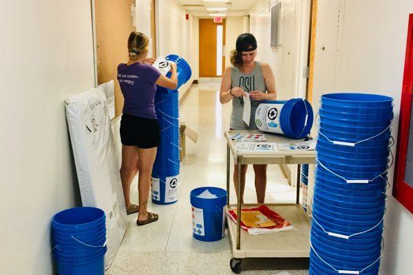 Students arranging mobile waste station