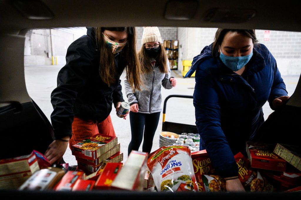 Pictured from left to right, undergraduate volunteers Danielle Wendricks, Izzy Boudnik and Julia Gutman with The Open Seat UW Student Food Pantry unload and sort nearly $500 in groceries at the Student Activity Center at the University of Wisconsin-Madison on Nov. 21, 2020. The student organization is preparing Thanksgiving dinner ingredient kits to be freely distributed to nearly 100 requesting students. All were wearing face masks and practicing safety protocols as the global coronavirus (COVID-19) pandemic continues. (Photo by Jeff Miller / UW-Madison)