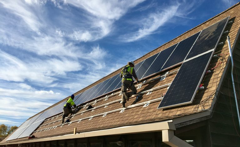 Solar installers installing the new solar array at the Arboretum visitor center