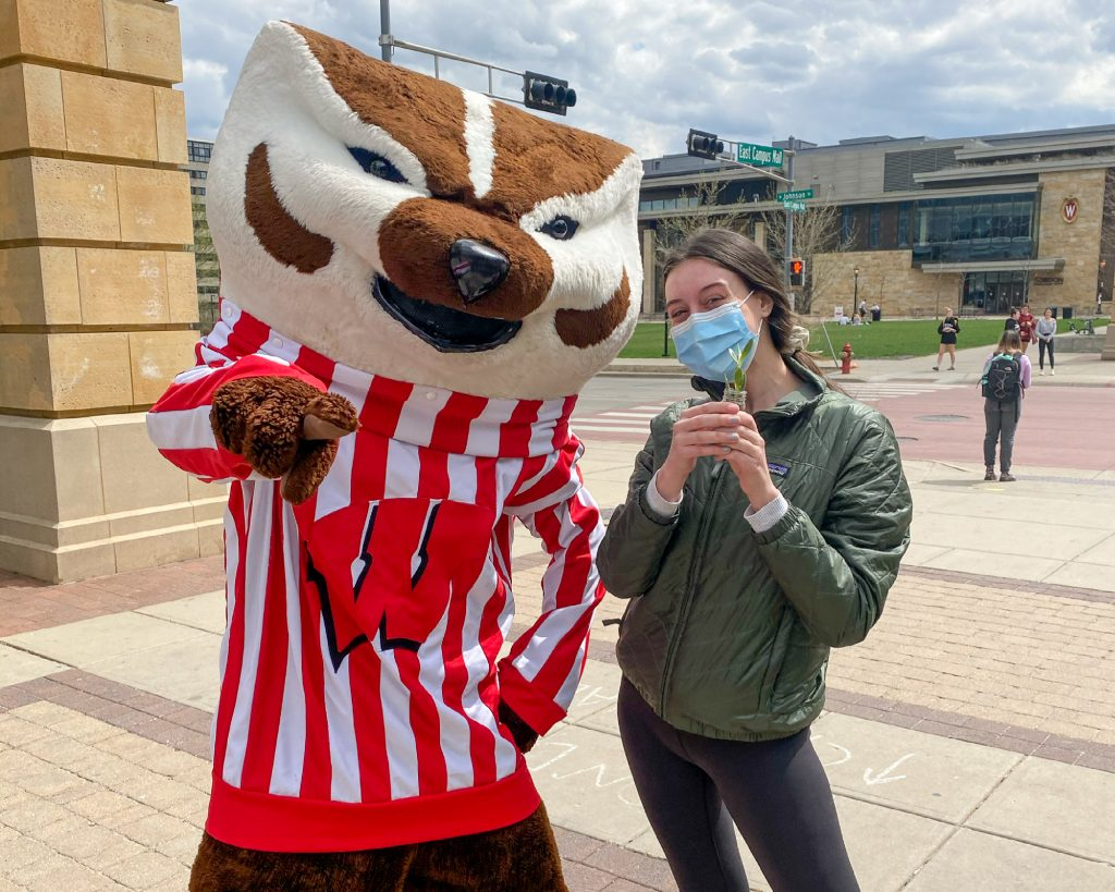 Natalie Tinsen poses with Bucky Badger during the plant giveaway hosted by Allen Centennial Garden, the ASM Sustainability Committee, and the Office of Sustainability.