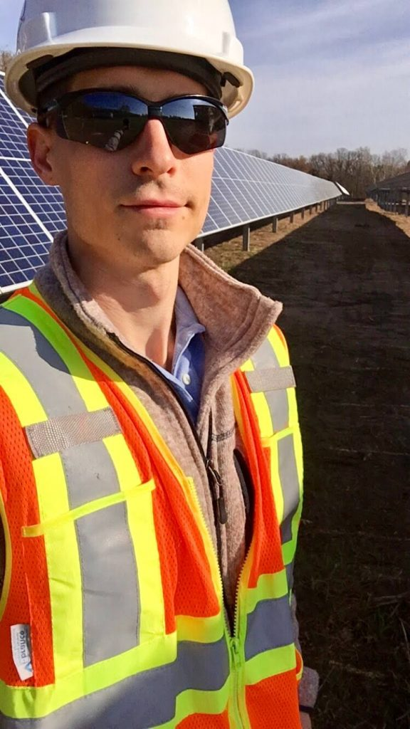 Photo of man standing in front of solar panels